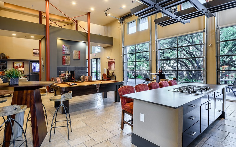Spacious and well lit game room with demonstration kitchen, pool table and large windows with a view of a oak tree
