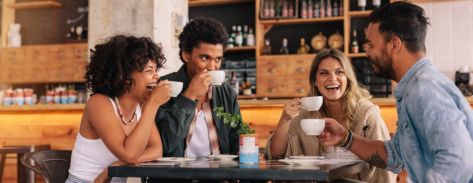 A group of friends sitting at a coffee shop laughing
